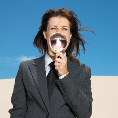 Woman with magnifying glass in her mouth in the desert.